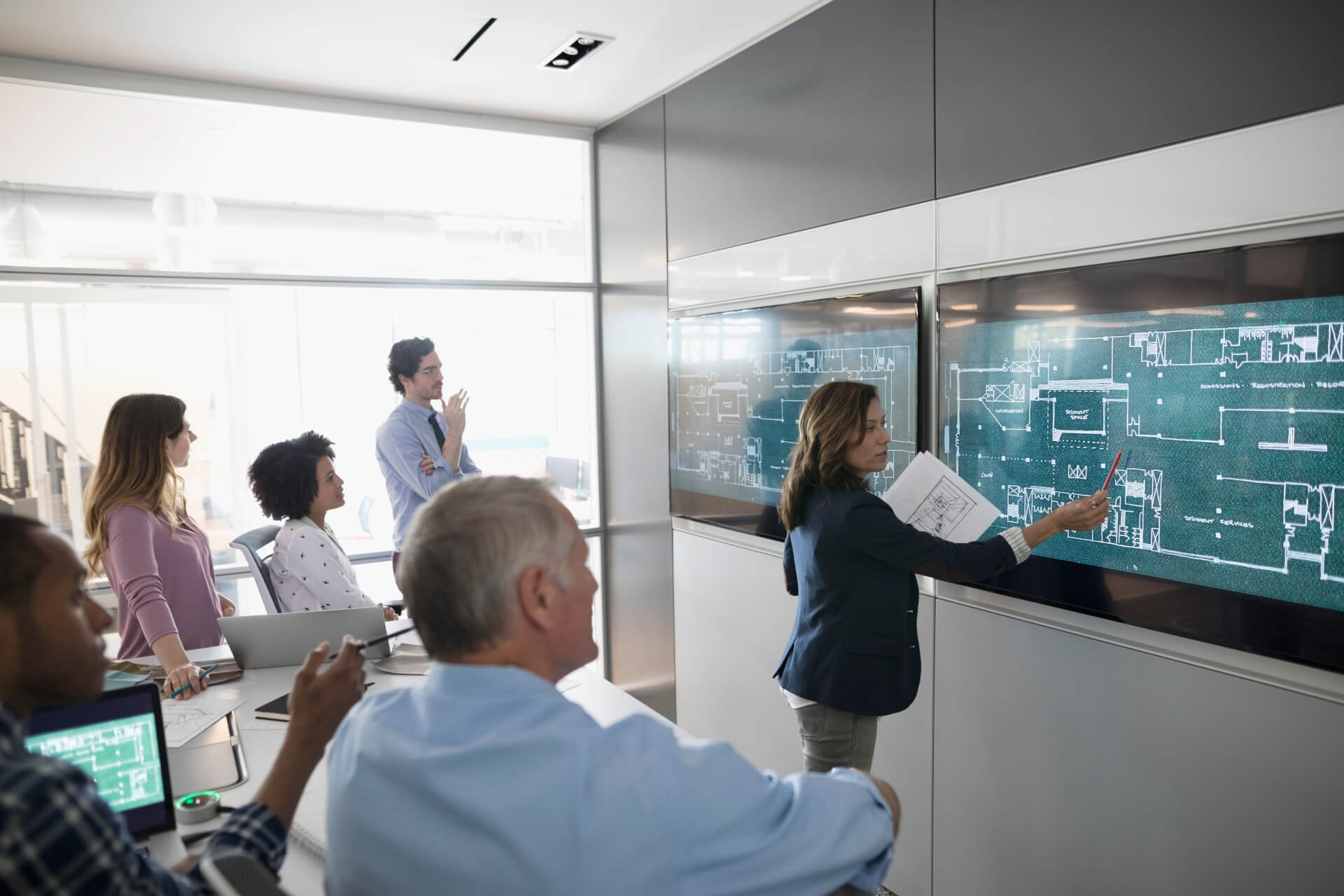 Female architect discussing digital blueprints at screen, leading conference room meeting