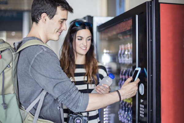 Young couple paying with mobile phone the soft drink at vending machine in the airport.